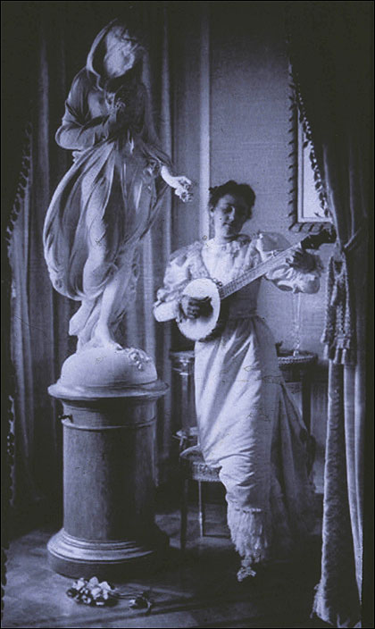 Miss Apperson playing banjo beside statue of Flora in niche of Sen. George Hearst's residence, Washington, D.C. The photograph  in 1895 by Frances Benjamin Johnston.jpg